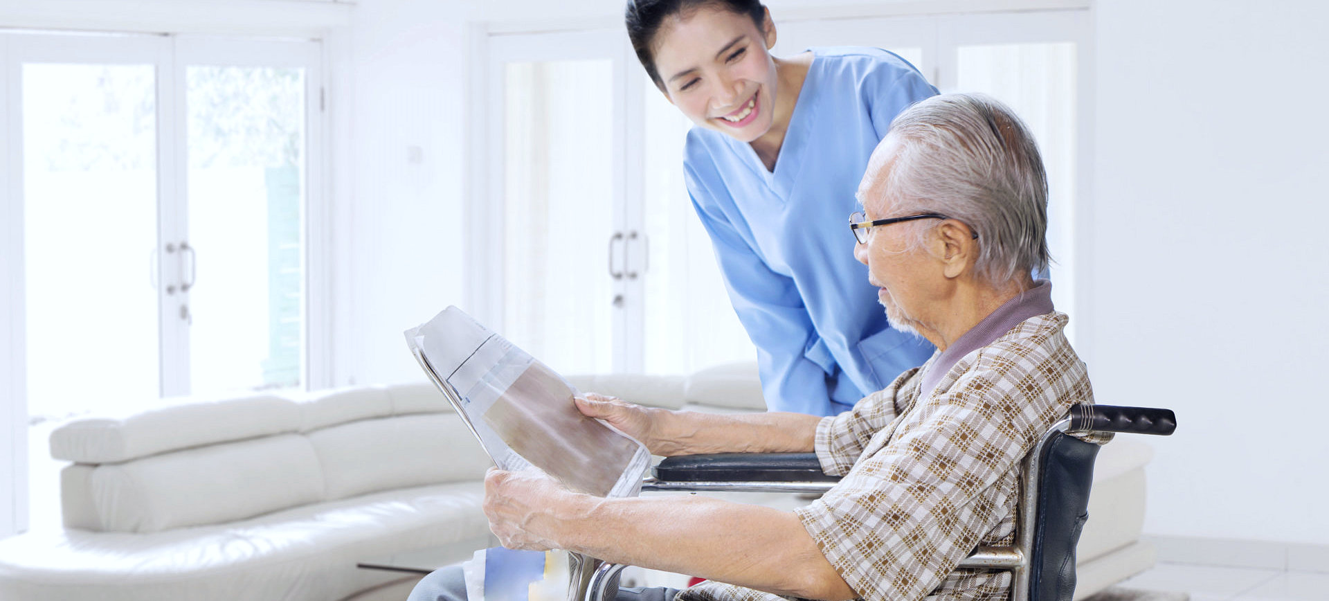 senior man reading a newspaper with his caregiver