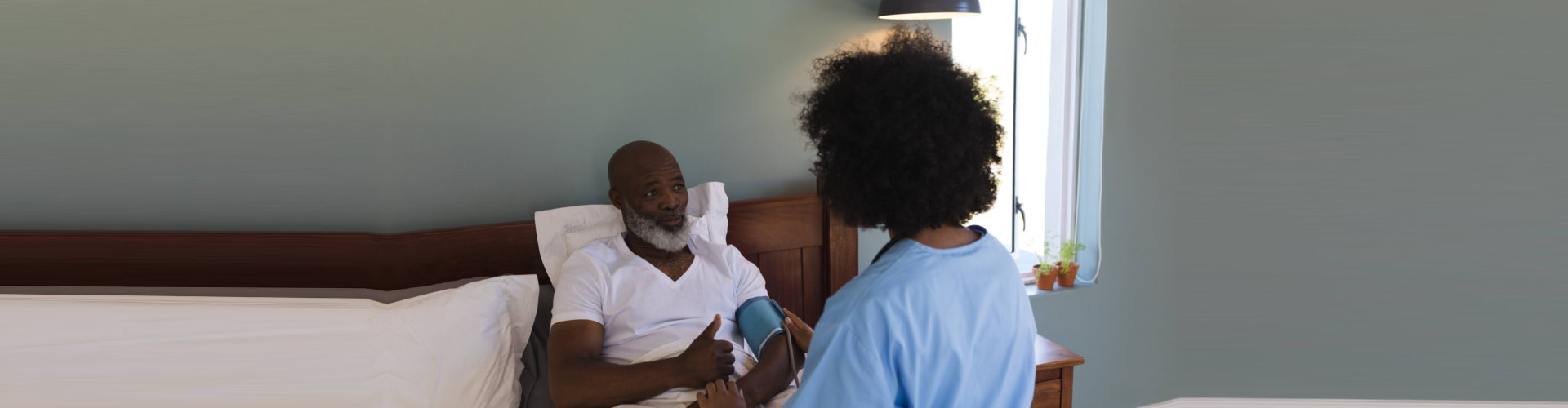 caregiver checking blood pressure of senior man