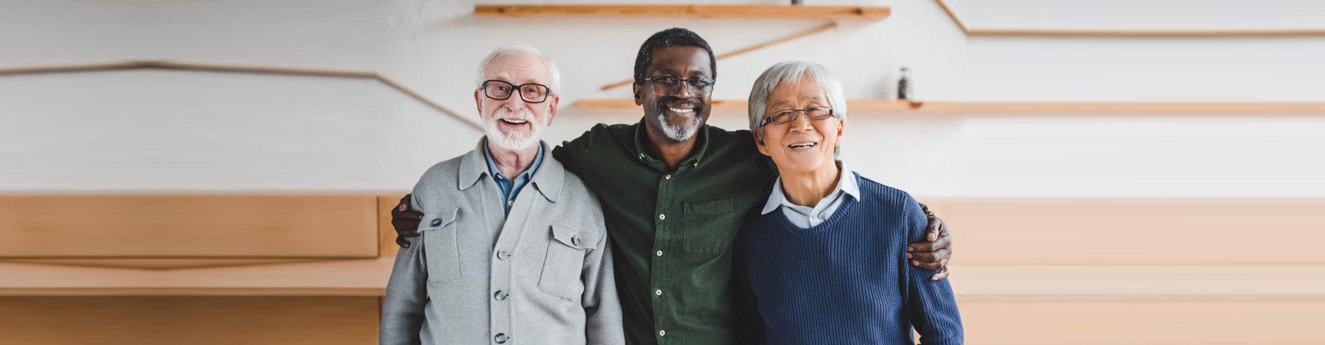 three senior men smiling